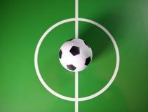 在一个中场戏弄soccerball,在绿色领域的中心 库存图片