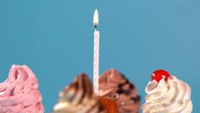在一个中央灼烧的蜡烛附近的转动的杯形蛋糕 影视素材