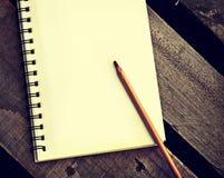在一个习字簿的纸与在木桌上的笔 免版税库存图片