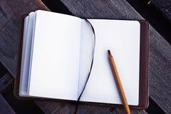 在一个习字簿的纸与在木桌上的笔 库存照片