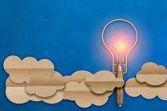 在一个云彩形状纸平的样式的电灯泡与木铅笔 库存照片