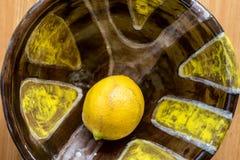 在一个五颜六色的陶瓷碗的黄色柠檬 免版税库存照片