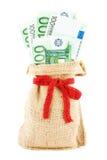在一个亚麻制大袋的欧元,包扎由礼物红色丝带 免版税图库摄影