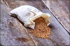 在一个亚麻制袋子的荞麦在一张老桌上 库存图片