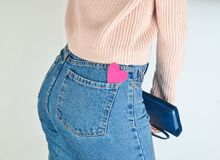 在一个亭亭玉立的女孩的牛仔裤的后面口袋的装饰心脏 库存照片