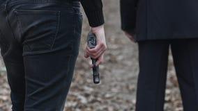 在一个人后的危险犯罪人身分衣服和在他的手上拿着的一杆枪 关闭 股票录像