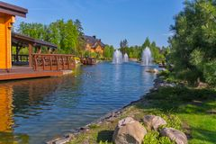 在一个人工湖的喷泉在木房子附近 露天放松的一个巨大地方 库存照片