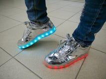 在一个人的脚的发光的LED运动鞋 库存图片