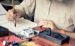 在一个传统日本技术Sumi-e的艺术家绘画 库存照片