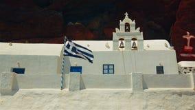 在一个传统白色Cycladic教会旁边的希腊旗子飞行有火山的红色峭壁的在背景中 股票录像