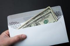 在一个信封的金钱在黑背景 免版税库存照片