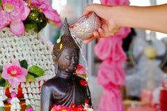 在一个修士雕象的男性手倾吐的花水在菩萨寺庙 免版税库存图片