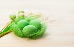 在一个假日之前上色在巢的鸡蛋,装饰品的 图库摄影