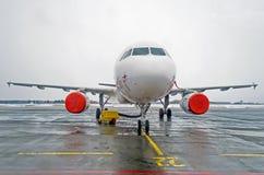 在一个停车场的乘客飞机与在恶劣天气的被覆盖的引擎 库存照片