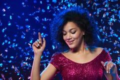在一个党的妇女跳舞在与五彩纸屑的五颜六色的背景 免版税库存图片