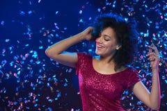 在一个党的妇女跳舞在与五彩纸屑的五颜六色的背景 免版税库存照片
