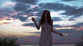 在一个党的无忧无虑的少妇跳舞在海滩 美丽的女孩画象有闪烁发光物的 女孩剪影在 股票视频