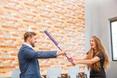 在一个公司党的办公室,一个人和女孩由棍子唬弄从五彩纸屑下面 免版税库存图片