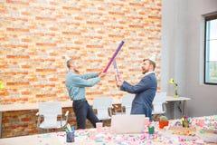 在一个公司党的办公室,人唬弄用棍子从五彩纸屑下面 库存照片