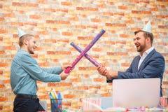 在一个公司党的办公室,人唬弄用棍子从五彩纸屑下面 免版税库存图片