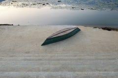 在一个具体堤防的一条被倒置的小船 免版税库存照片