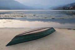 在一个具体堤防的一条被倒置的小船 免版税库存图片