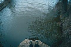 在一个具体水坝边缘的腿在河附近 库存图片