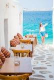 在一个典型的希腊室外咖啡馆的室外咖啡馆在米科诺斯岛有在基克拉泽斯海岛上的惊人的海视图 免版税库存照片