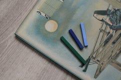 在一个册页的五颜六色的蜡笔画的在木背景 儿童` s发展的学校辅助部件 皇族释放例证