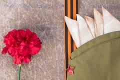 在一个军用盖帽的被折叠的信件有一个星、圣乔治丝带和一朵红色花的在一封老信件的背景 图库摄影
