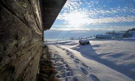 在一个农厂房子旁边的脚印雪的 免版税库存照片