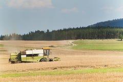 在一个农场的联合收割机收获成熟麦子在捷克 苹果庭院地面收获成熟时间结构树 五谷的耕种在一个农业农场的 库存图片