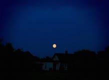 在一个农村小屋上的月亮 免版税库存图片