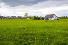 在一个农村房子附近的春天草甸 免版税库存图片
