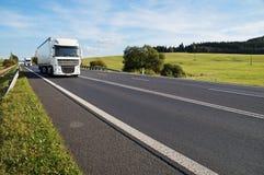 在一个农村风景的柏油路 在路的到达的两辆白色卡车 库存图片