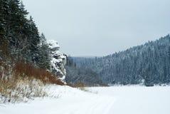 在一个冬天结冰的池塘的岸的一个美丽如画的岩石山的 图库摄影