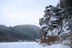 在一个冬天结冰的池塘的岸的一个美丽如画的岩石山的 免版税库存图片