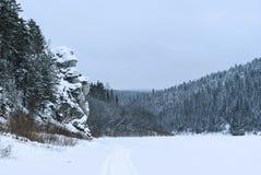 在一个冬天结冰的池塘的岸的一个美丽如画的岩石山的 免版税图库摄影