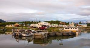 在一个冰河湖旁边和小游艇船坞的营地位于育空地区的一个遥远的部分 免版税库存照片