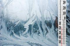 在一个冷淡的冬天窗口的温度计 免版税库存图片