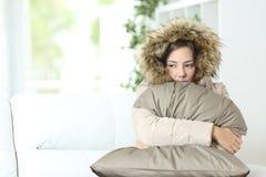 在一个冷的家温暖地穿衣的妇女 免版税库存照片