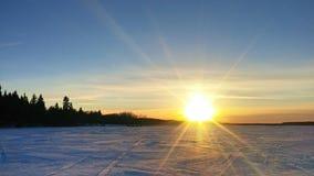 在一个冻冬天湖的日落 免版税库存图片