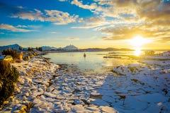 在一个冻湖的低潮期间与冰中小型的片断的惊人的日落视图忘记了 库存图片