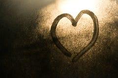 在一个冻窗口画的心脏在冬天 免版税库存图片