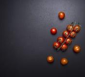 在一个分支的新鲜的水多的西红柿在黑板边界,文本木土气背景顶视图的地方 库存照片