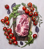 在一个切板有菜的,草本木土气背景顶视图关闭的新鲜,可口未加工的猪肉牛排 图库摄影