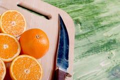 在一个切板的切的成熟开胃桔子在一绿色tabl 库存图片