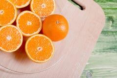 在一个切板的切的成熟开胃桔子在一绿色tabl 免版税图库摄影