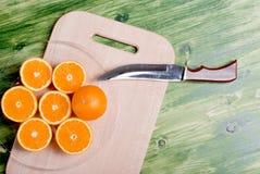 在一个切板的切的成熟开胃桔子在一绿色tabl 图库摄影