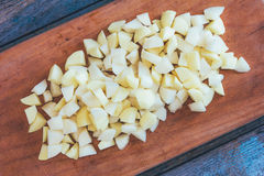 在一个切板的切的未加工的土豆在一张老土气木桌上 库存照片